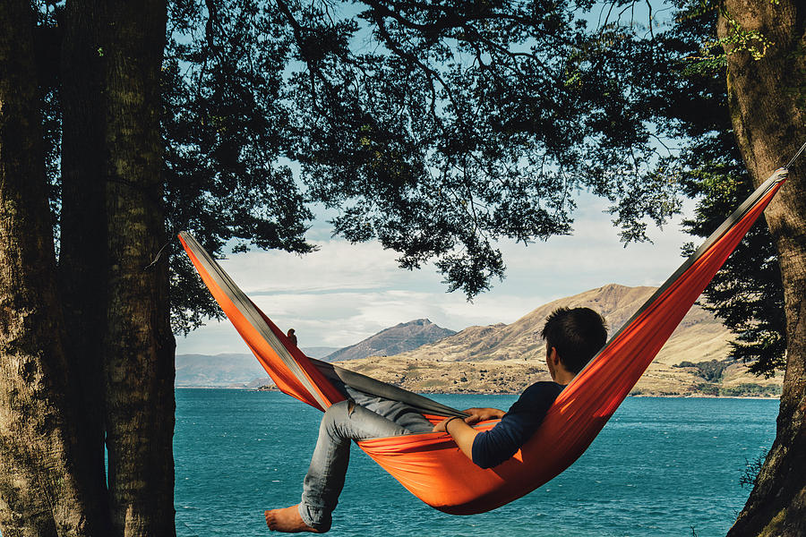 This image has an empty alt attribute; its file name is guy-in-hammock-looking-at-the-lake-mathieu-b-morin.jpg